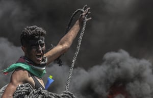 A Palestinian protester holds rope during clashes near the border with Israel in the east of the Gaza Strip