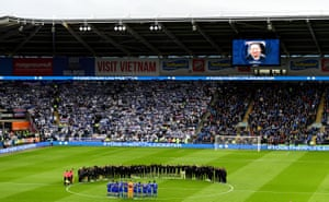 Leicester City players and staff stand with Cardiff City players and match officials during a minute's silence in memory of the victims of the Leicester City helicopter crash.