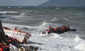 Volunteers assist people on a rubber boat near the Greek coastline.