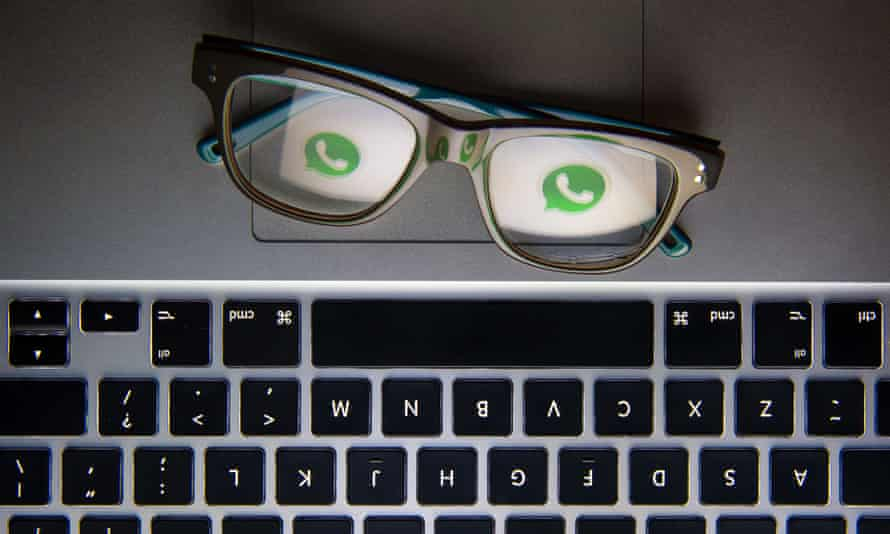 the whatsapp logo reflected in the lenses of a pair of glasses resting on a laptop
