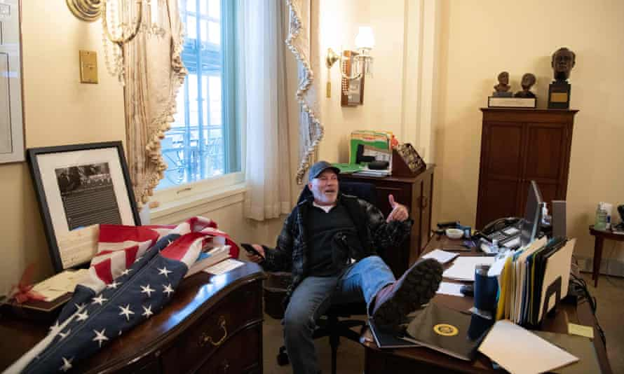 Richard Barnett, a pro-Trump supporter sits inside the office of Speaker of the House Nancy Pelosi as he protest inside the US Capitol on 6 January.