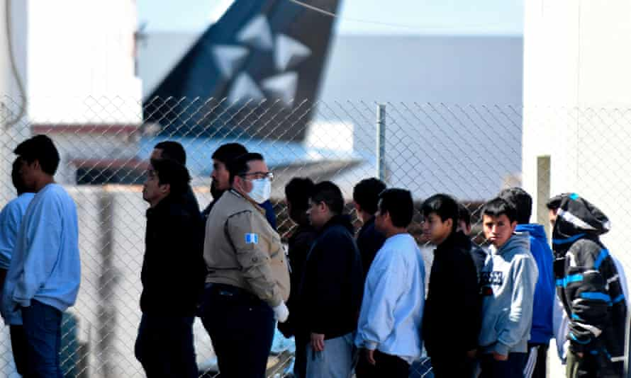 An immigration official in Guatemala oversees the arrival of migrants deported from the US.