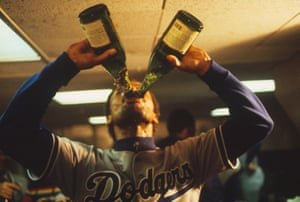 Derrel Thomas of the Los Angeles Dodgers guzzles two bottles of champagne during the team's victory celebrations after defeating the New York Yankees for the 1981 World Series