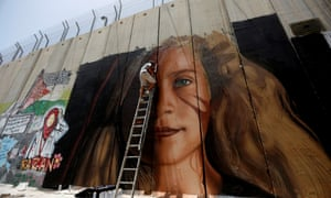 One of the two Italian artists works a mural of Ahed Tamimi on the Israeli separation barrier.