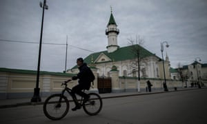 A cyclist rides in front of the Märcani mosque.