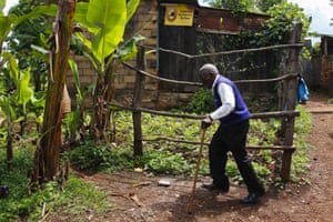 Mbiuki walks through his village back to his dilapidated shack