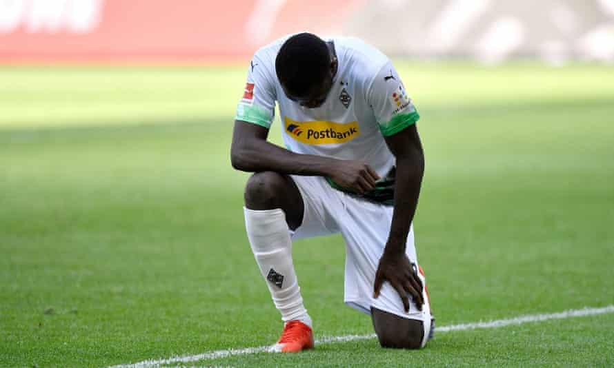 Marcus Thuram kneels after scoring a goal.