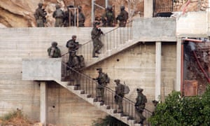 Israeli soldiers deploy near a Palestinian house