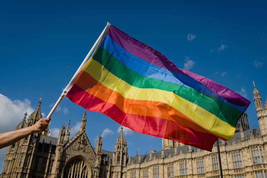 A protester holds a rainbow flag outside the Houses of Parliament in central London in 2013 as people gather in support of same-sex marriage.