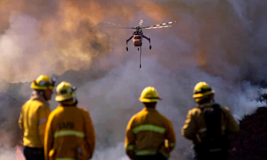 Firefighters look at the rotation of helicopters dropping water on the Getty fire spreading in the hills behind the Getty Center.