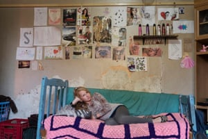 A girl who wants to be a model sits on her bed in her room