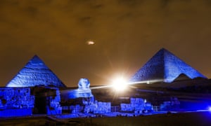 The Great Pyramids of Giza is lit up blue in Giza, Egypt