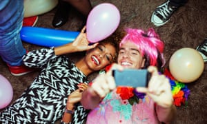 Couple taking self-portrait with cell phone on floor at party. Image shot 2013. Exact date unknown.<br>DTKCGD Couple taking self-portrait with cell phone on floor at party. Image shot 2013. Exact date unknown.
