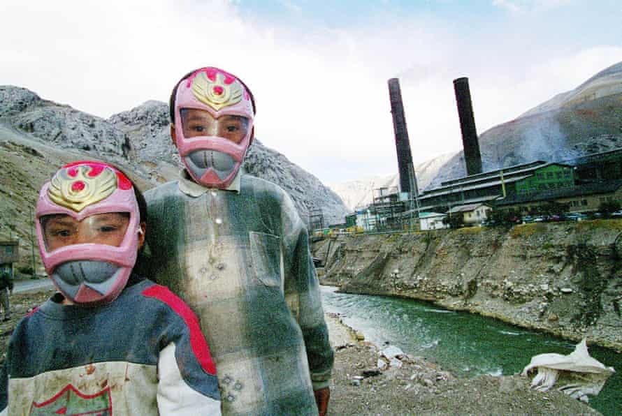 Children wearing masks play near the poly-metal smelter in La Oroya, owned by the US company Doe Run, in Peru's central Andes. This photo was taken in 2000.