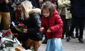 A girl places a candle in front of Paris's Carillon cafe on Saturday 14 November.