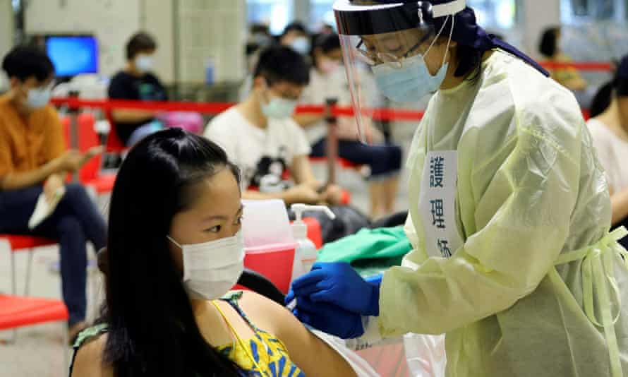 A medical worker administers a dose of the domestically developed Medigen vaccine to a patient in Taipei, Taiwan.