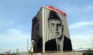 A man cleans a picture of Muhammad Ali Jinnah, the founder of Pakistan, in Karachi.