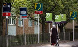 A pedestrian pushes a baby stroller as she walks past estate agent signs in the Kingston area of London