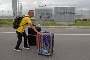 A passenger walks to the airport as pro-democracy protesters blocked a road outside the Hong Kong airport, September 1, 2019.