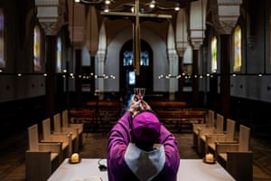 The auxiliary bishop of Lyon, Emmanuel Gobilliard, rehearses before holding a streamed live mass in the empty Saint-Irenee church on Tuesday