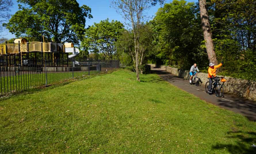 An urban green space with two cyclists
