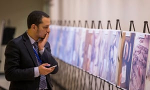 A man reacts as he looks at some of Caesar's photographs, at the UN in New York.