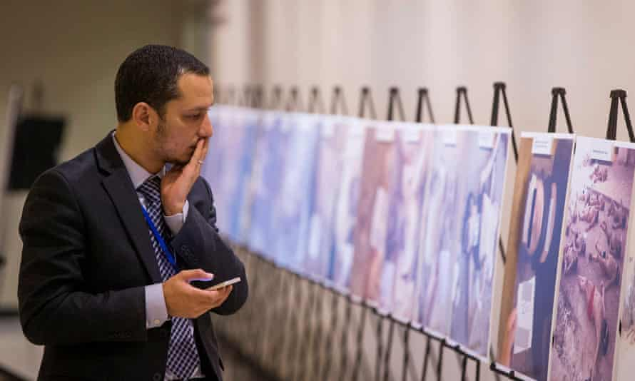 A man reacts as he looks at a gruesome collection of images of dead bodies in Syria