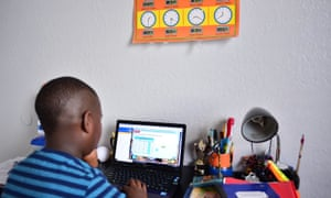 A nine-year-old student Jordan takes part in distance virtual school learning from his bedroom in Broward county, Florida.