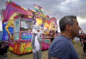 A person dressed as a rabbit stands by a food stall in Titu
