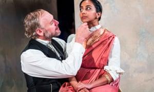 Anjana Vassan's Niru sits on Elliot Cowan's knee as he fondles her chin, in A Doll's House