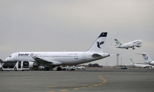 A Iranian Mahan Air passenger plane takes off as a plane of Iran's national air carrier, Iran Air, is parked at left, at Mehrabad airport in Tehran, Iran.