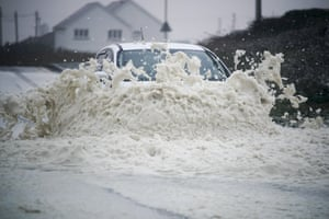 A car drives through sea foam whipped up by the wind of Hurricane Ophelia at Trearddur Bay in Holyhead, Wales