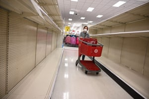 Burbank, USA shopper walks by shelves in the paper products aisle of a store as paper towels and other cleaning supplies are flying off retail shelves amidst a new wave of panic buying