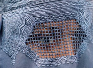 A close up shot of a woman in a burqa with mesh covering her eyes