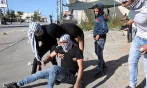 Palestinians tend to a protester injured during clashes in the West Bank.