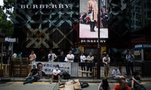 Demonstrators gather in front of a Burberry store in Hong Kong's Tsim Sha Tsui shopping district.