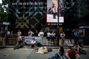 Demonstrators and bystanders gather in front of a Burberry Group Plc store on Canton Road in the area of Tsim Sha Tsui in Hong Kong, China.
