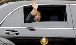 Kim Jong-un waves from a car after arriving by train in Dong Dang