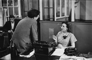 Women Reporters, 1952. A female reporter sits at her desk while chatting with a colleague