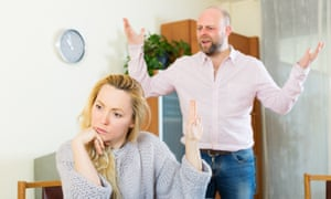 Angry couple during quarrelAngry guy and woman during quarrel in living room