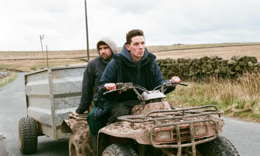 Actors Alec Secareanu and Josh O'Connor on a tractor in a scene from the film God's Own Country