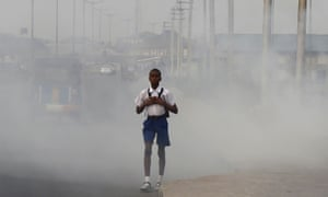 A school boy walks past smoke and fumes emitted from a dump in Port Harcourt.
