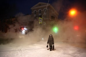 A woman clad in black walks in a snowbound street after dark