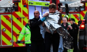 Police assist an injured man near London Bridge after the suspected stabbing attack