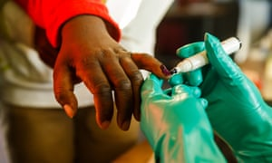 An elections officer applies indelible ink to a voter's finger in Zimbabwe