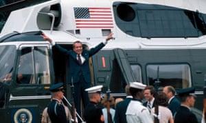 Richard Nixon fait des gestes à la porte de l'hélicoptère après avoir quitté la Maison Blanche à la suite de sa démission suite au scandale du Watergate, le 9 août 1974.