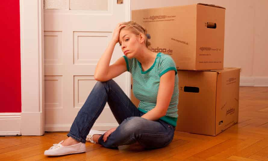 Young woman sitting in front of moving boxes