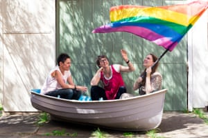 Jackie Braw, Vicki Harding and Brenna Harding in a small boat with a rainbow flag