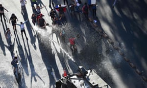 Riot police fire a water cannon to disperse demonstrators at La Alameda in Santiago on Monday.
