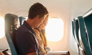 Smiling couple reading magazine on airplane